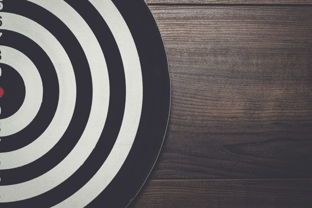 darts target on dark wooden background
