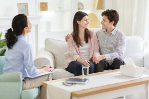 Happy couple at successful therapy session with family psychologist