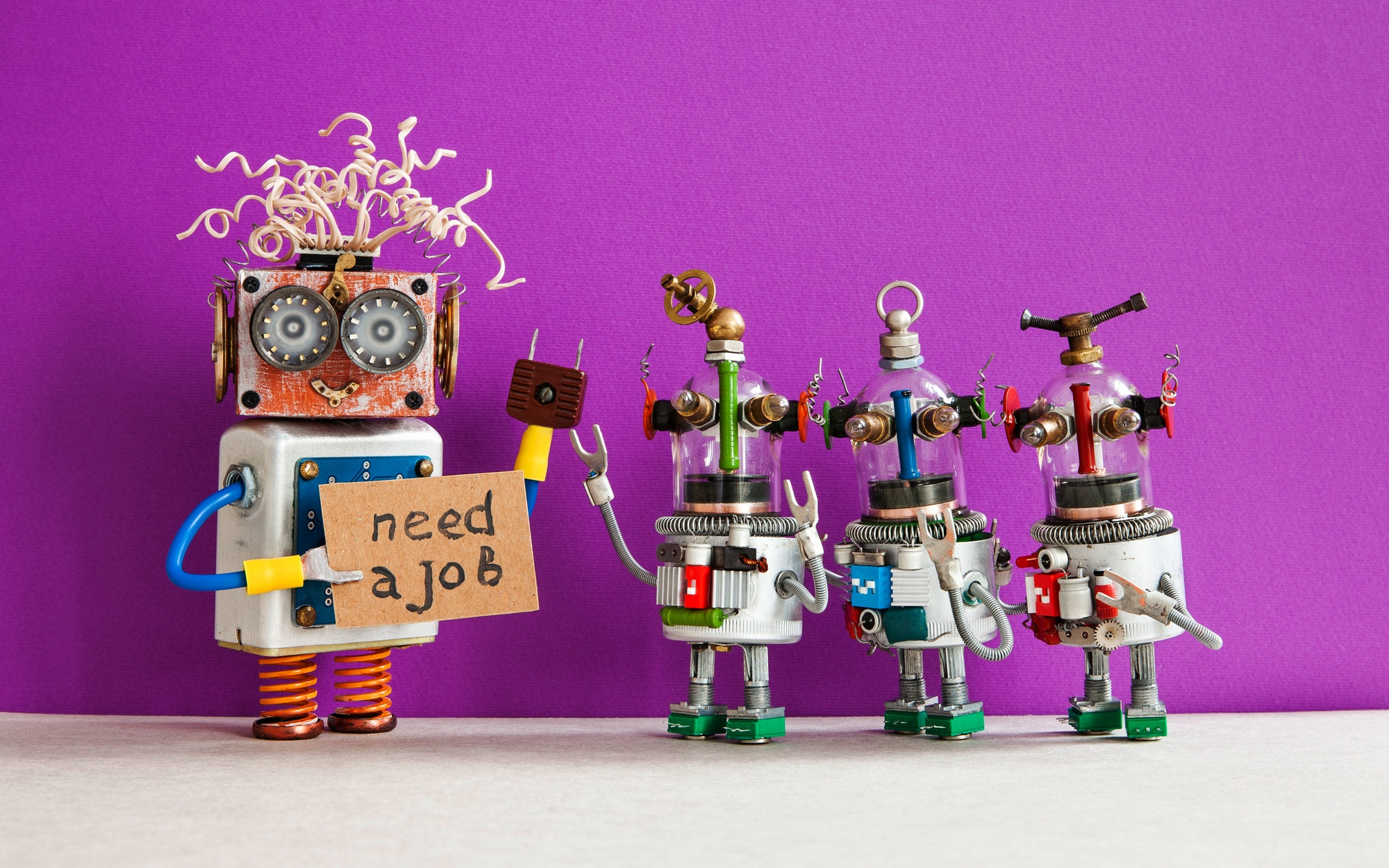 Job search concept. Robots looking for a job. Smiley unemployed robotic character with friends