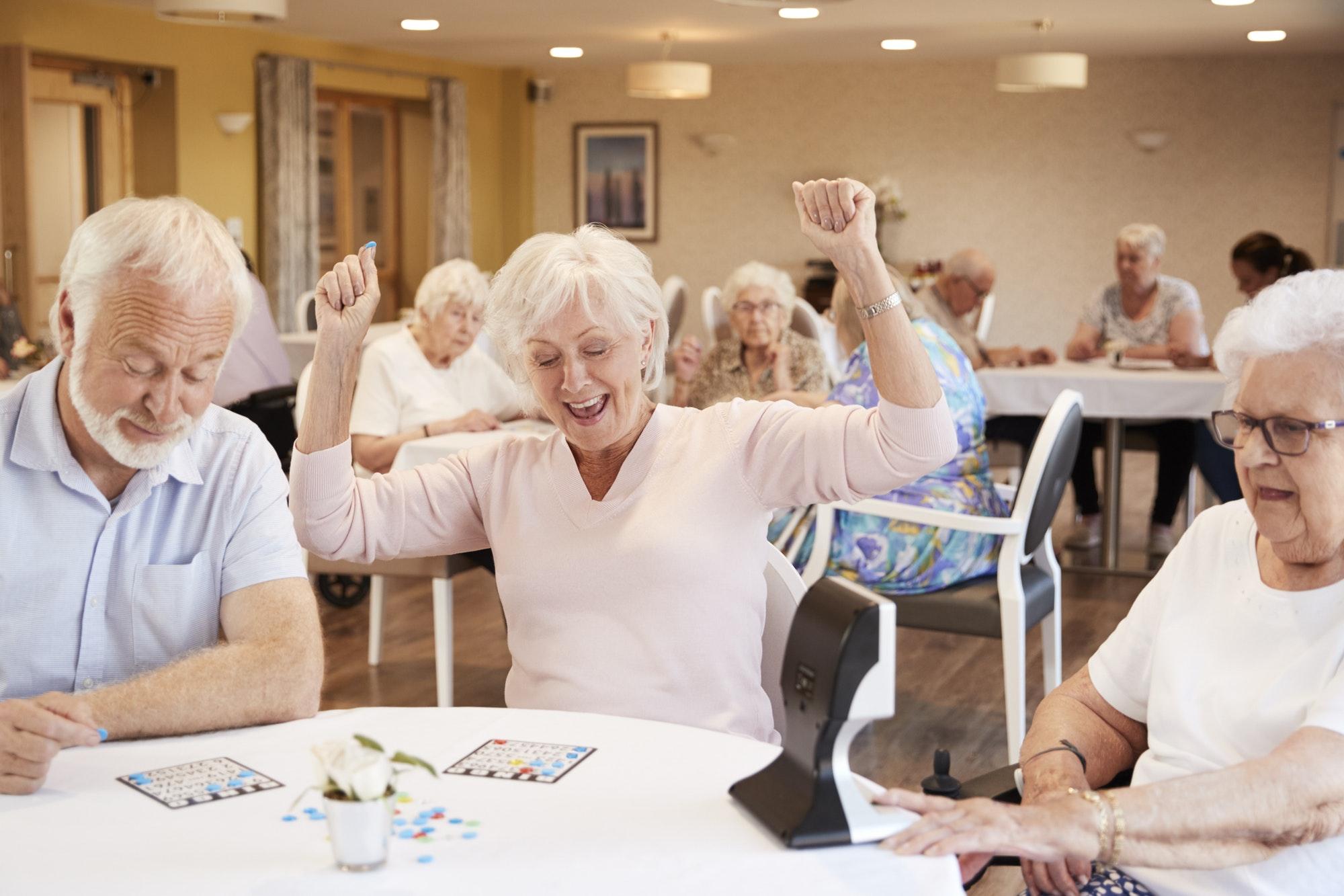 Senior Woman Winning Game Of Bingo In Retirement Home