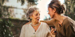 joyful adult taking care of an elderly woman