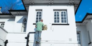 a man painting a house white