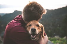 man embracing pet dog