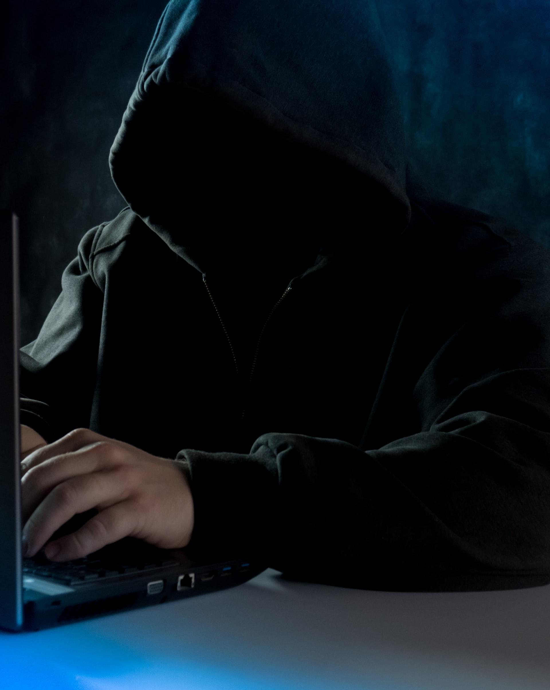 anonymous computer hacker in hoodie using laptop