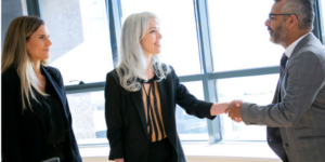 two women one man woman shaking hands