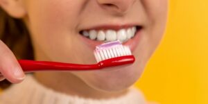 a girl who smiles and brushes her teeth with a red toothbrush on a yellow background